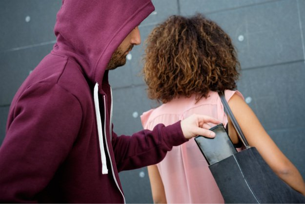 man-in-hoodie-stealing-wallet-2 Holiday Shopping Safety Tips: How To Prevent Purse Snatching