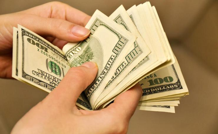 Woman hands counting us dollar banknotes | Travel Safety Tips You Shouldn't Ignore