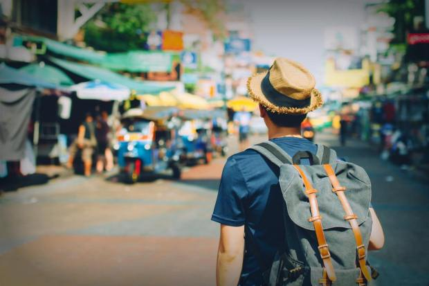 Young Asian traveling backpacker in Khaosan Road outdoor market | Travel Safety Tips You Shouldn't Ignore
