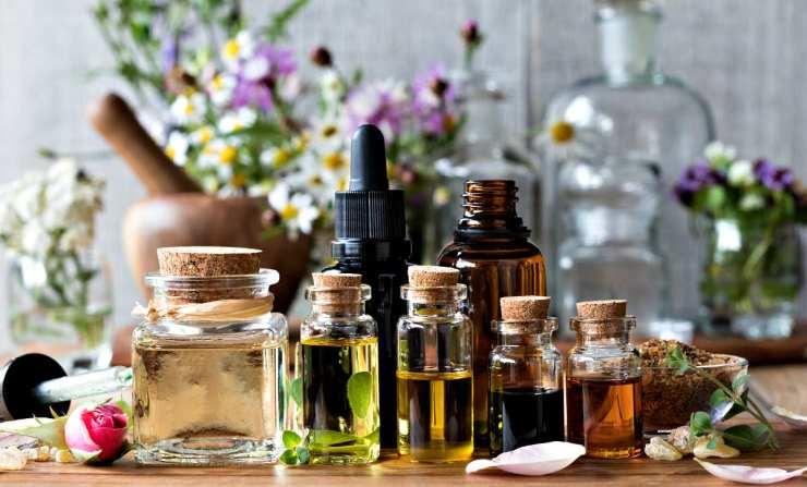 Selection of essential oils, with herbs and flowers in the background | Ways To Remove A Splinter