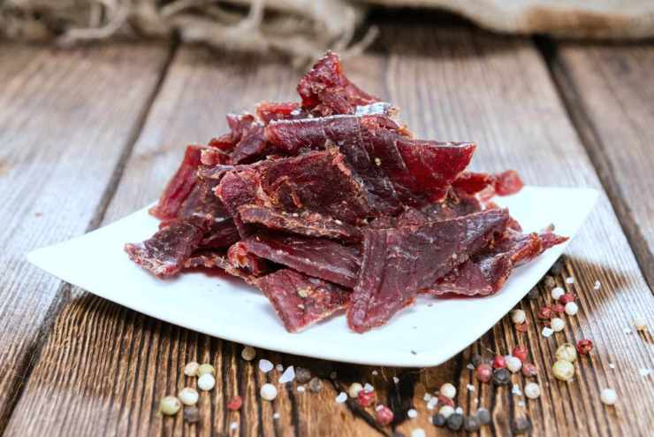 portion of beef jerky on wooden background | DIY Survival Food You'll Actually Want To Eat | survival food | emergency food