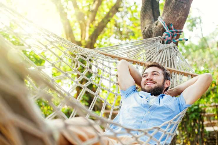 man swinging on a hammock | How Camping In The Rain Can Prepare You For A Disaster