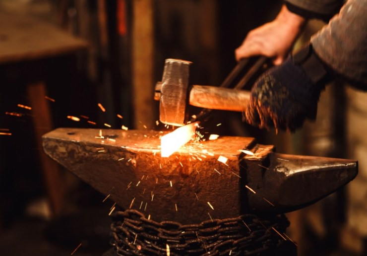 blacksmith manually forging redhot metal on | blacksmith forge