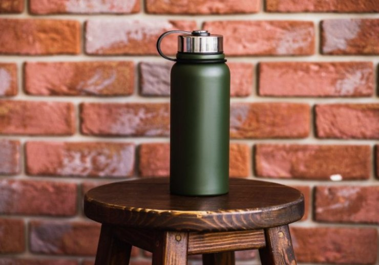 thermos bottle near brick wall background | winter survival