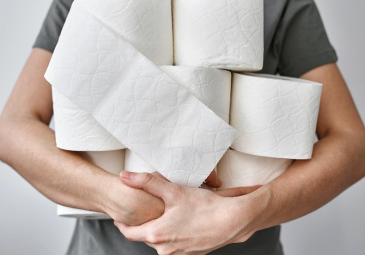 woman holds many rolls toilet paper | best prepper supplies