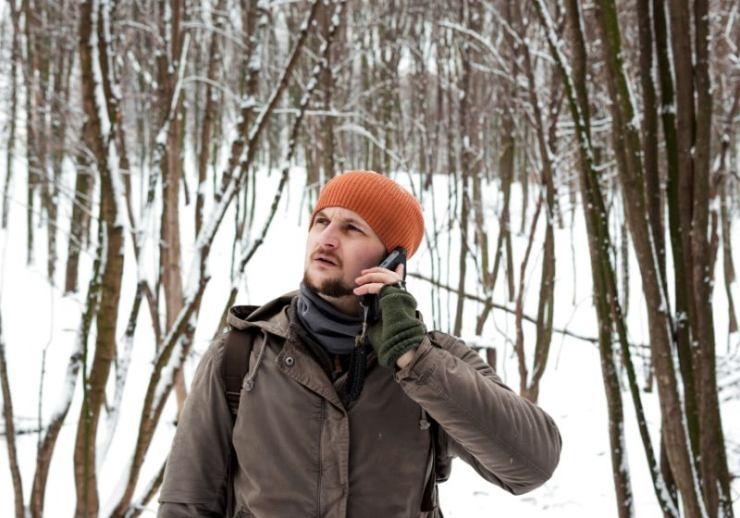 man uses mobile phone snowy forest | solar charger battery