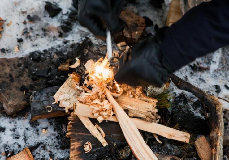 man starts fire magnesium steel striker   winter survival gear