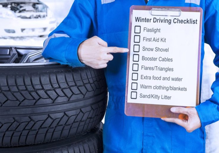 car mechanic leaning on a pile of tires and showing a winter driving tips on the clipboard | winter driving tips | winter driving checklist