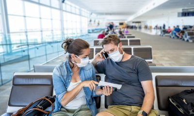 COVID-19 worldwide borders closures. Couple with face mask stuck in airport terminal after being denied entry to other countries-Coronavirus State Restrictions-ss-featured