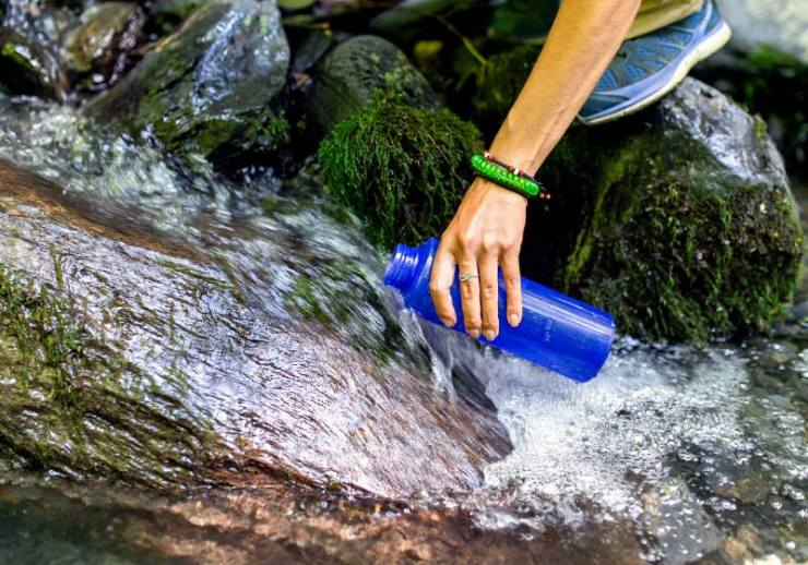 beautiful woman taking water forest spring | potable water definition