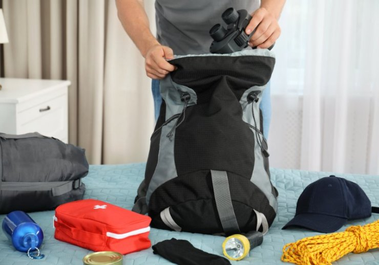 man packing different camping equipment into | new year resolutions ideas