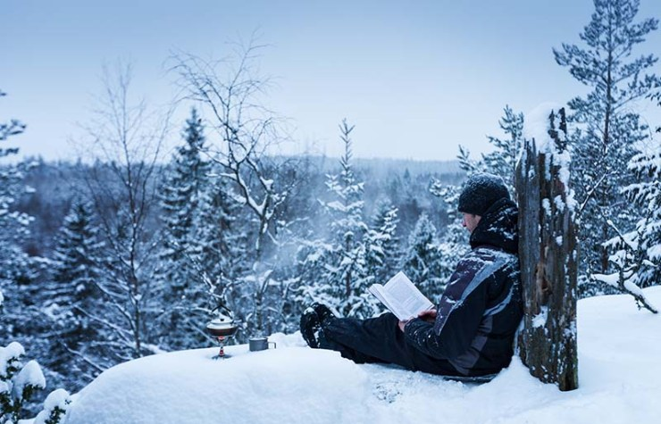 man reading book located on hill | how to prepare for an avalanche