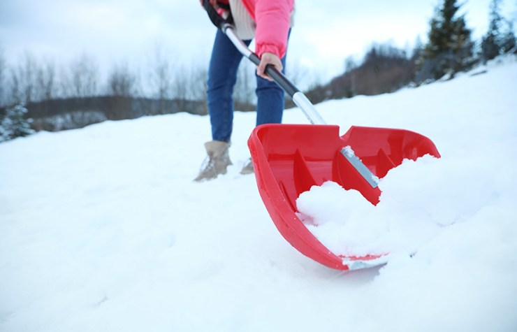woman cleaning snow shovel outdoors on | how to build a quinzee