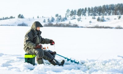 A young man is fishing from a hole on ice | Ice Fishing 101 | Everything You Need To Know | featured