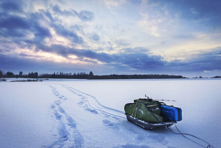Winter fishing sled with equipment for ice fishing on the snow-covered lake | urban dictonary