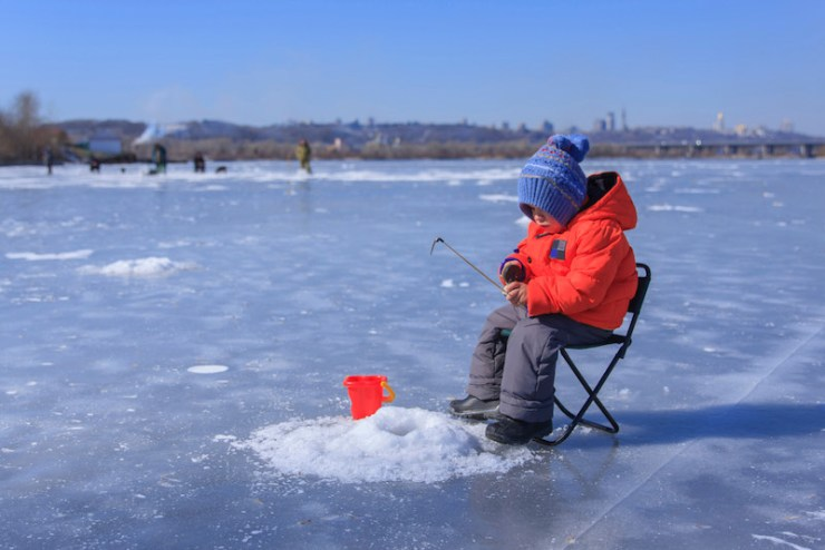 a little boy in winter clothes is fishing on a frozen lake | ice fishing tips