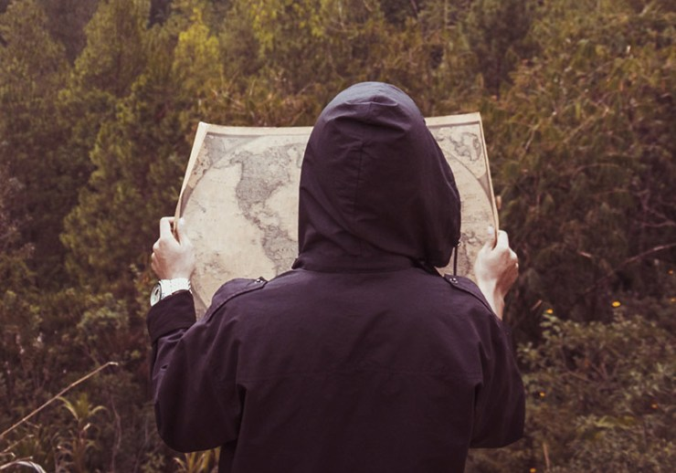 person with map in the woods | backpacking checklist