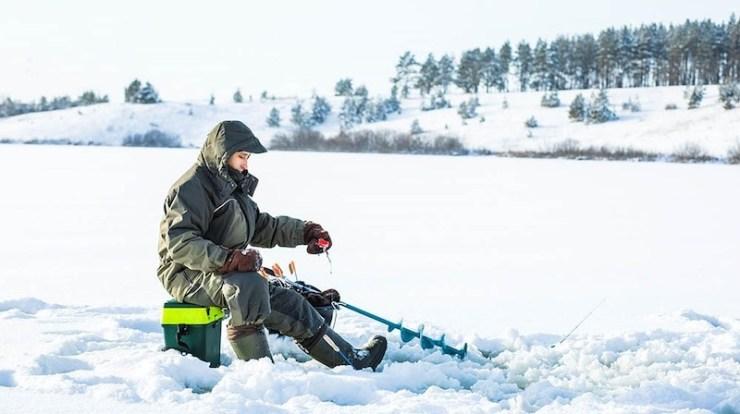 young man fishing hole on ice | ice fishing Minnesota