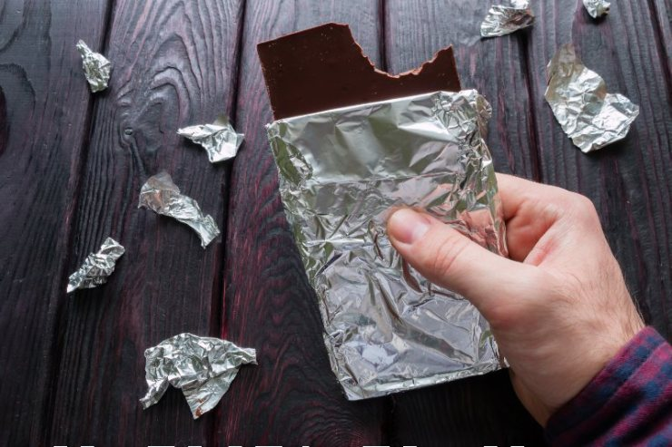 man eating a bar of chocolate on a black background-Food Kit-SS