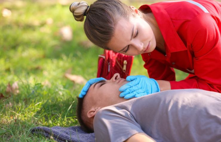 woman uniform checking breathing unconscious man | wilderness first aid