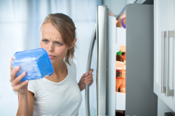 young woman in her kitchen by the fridge, looking at the expiry date-Food Kit-SS