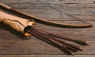 Close up shot of bow laying beside arrows in a leather quiver on wooden planks | DIY BOW AND ARROW | FOLLOW THESE SIMPLE STEPS | Featured