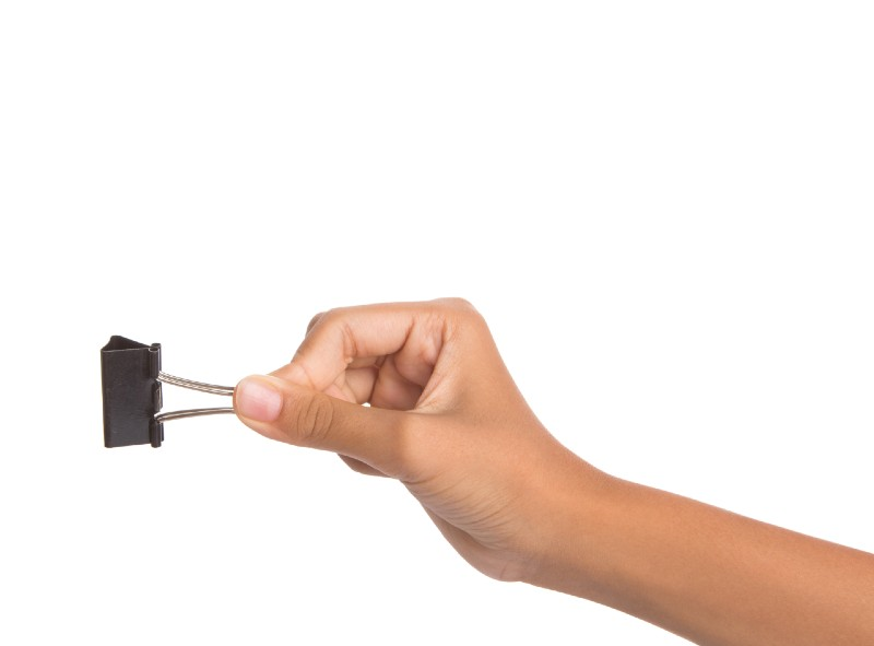 Female hand holding binder clip over white background-binder clip