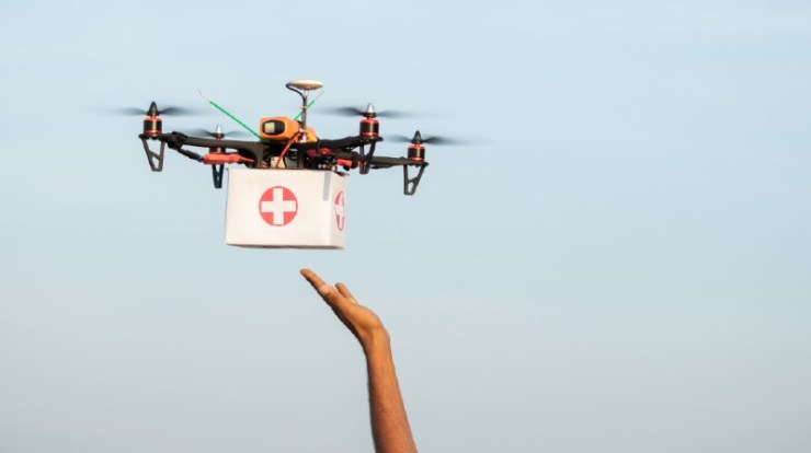 Hands reciving medical aid kit or medicins from drone or quadcopter during covid-19-IFAK