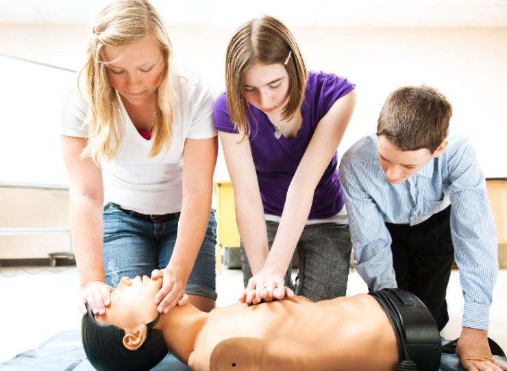 Students practicing CPR life saving techniques on a mannequin-first aid kits