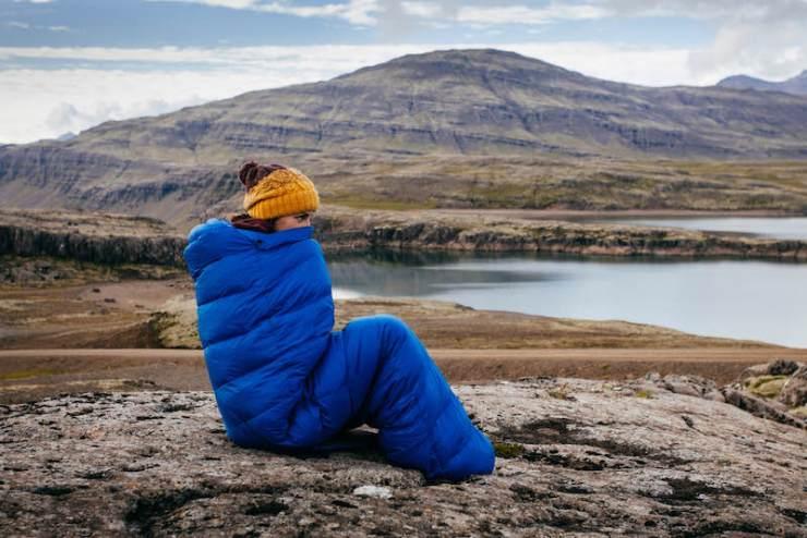 Young woman in warm blue sleeping bag | Emergency bag list