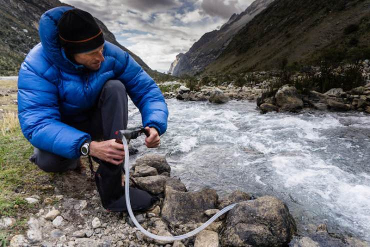 Man in blue down jacket filtering water | Emergency bag list