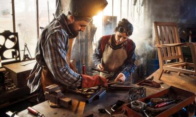 Two artisans welder in their craft workshop welding metal parts to assemble them on a designer wooden armchair. A man and a woman | How To Make A War Hammer | Featured