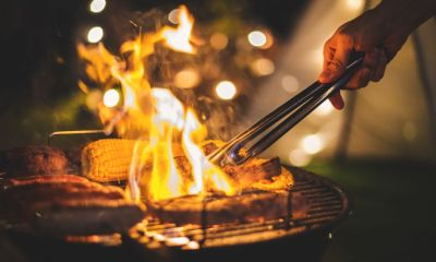 Family making barbecue in dinner party camping at night | 23 Best Camping Recipes | Featured