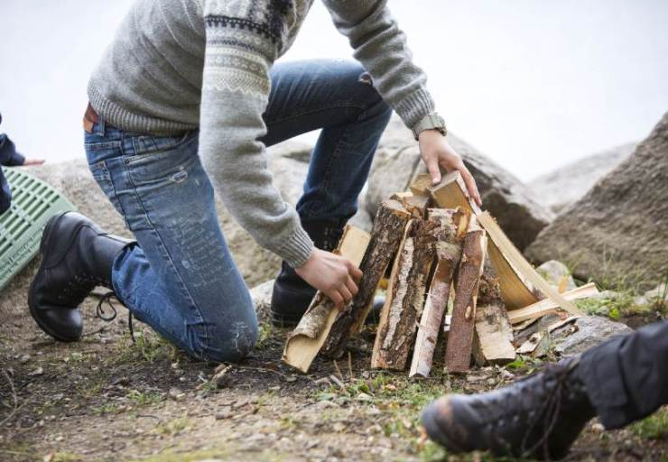 Man Arranging Firewood For Bonfire On Lakeside Camping-campfire