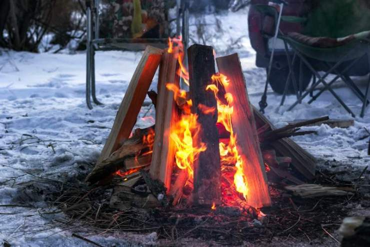 Red flames of teepee campfire on snowy ground at campsite-Types of Campfires