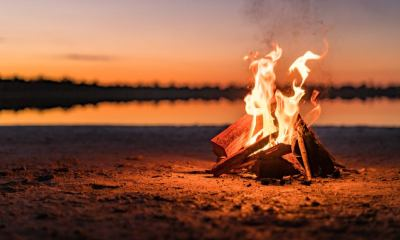 Small campfire with gentle flames beside a lake during a glowing sunset | The 5 Most Basic Types of Campfires And What They're For | featured