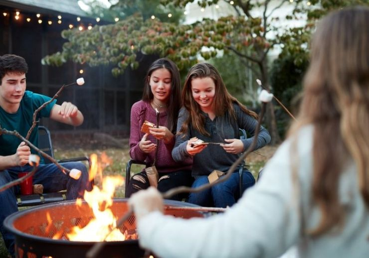 Teenage friends making samores | How to Book a Campsite from Parks to RVs to Backyards