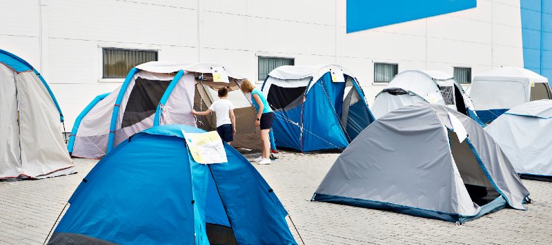 Woman and boy choose a camping tent in the store-tent