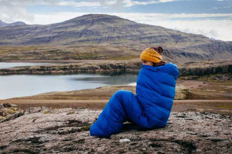 Young woman in warm blue sleeping bag , on the stones with northern mass-sleeping bag