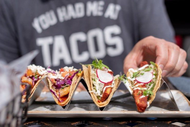 closeup of man eating tacos outside in summer-Fish Recipes