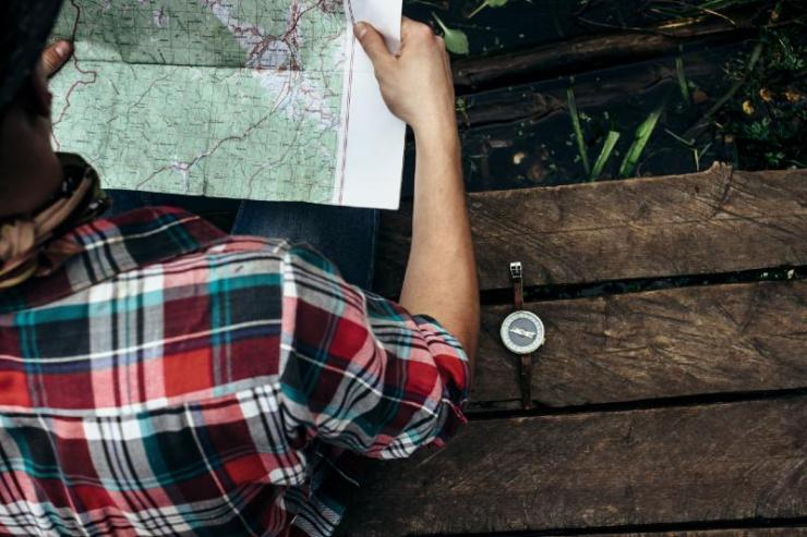 stylish hipster traveler exploring map at sunny forest and lake in the mountains-Camping Without Electricity
