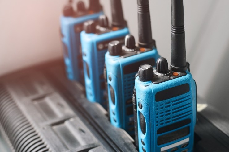 A set of blue walkie-talkies stand in a row-Emergency Radios