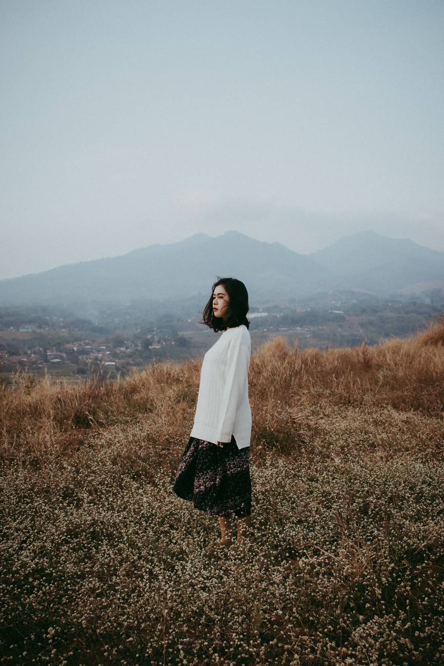 woman in white long sleeved top and skirt standing on field