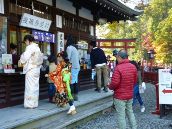 Clad in kimonos, mother and daughter pay at the cashier to cross the bridge.