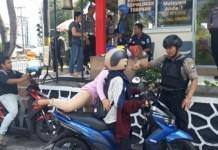 Personel Polres Tanjungpinang memberhentikan pengendara motor saat akan memasuki mako polres Tanjungpinang, Rabu (13/11/2019). (MBA/SURYAKEPRI,COM)