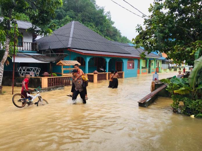 Personel Polsek Tambelan saat membantu warga yang terdampak banjir bah di tiga desa Kecamatan Tambelan, Bintan (suryakepri.com/istimewa)