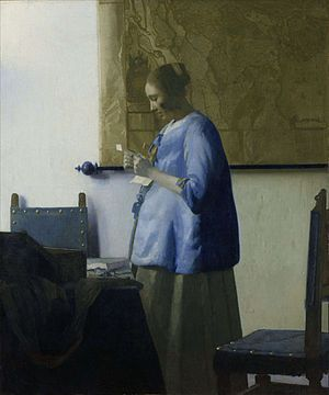 Mujer de azul leyendo una carta
