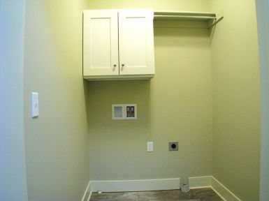 Laundry hook up with cabinets & clothes hanging bar