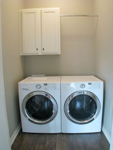 Laundry with washer, dryer, storage cabinet & clothes hanging bar.