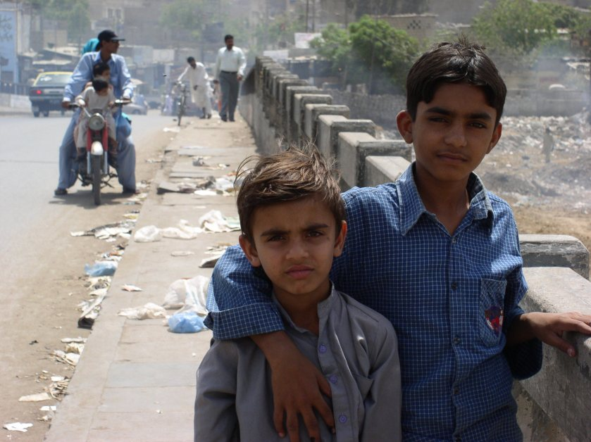two boys standing on a street with trash littered all around